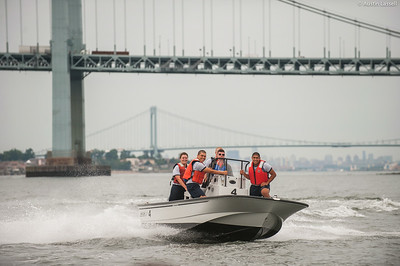 Midshipman William Lassell 3rd Classman at the helm of a Whaler with 4th Company candidates aboard returning to campus following obstacle course training at SUNY Maritime College on July 16th, 2014. Prominently in the background Throggs Neck Bridge can be seen and farther White Stone Bridge.