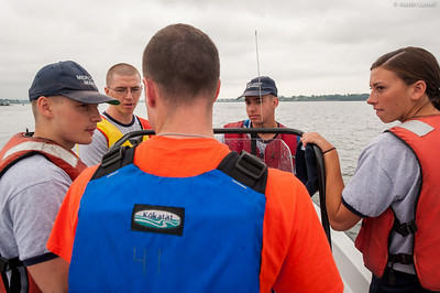 4th Company candidates listen closely to Midshipman William Lassell 3rd Classman, at the helm,  during small boats class on July 16th, 2014. Midshipman Lassell is giving the candidates proper instruction on the operation of a small boat, in this case a Whaler.