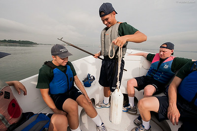 A 1st Company Platoon 102 candidate excitedly holds a boat bumper that he just successfully retrieved during a man overboard operation simulation during a  small boats class taking place on July 14th, 2014. This candidate, and his other fellow candidates are on board a Launcher being piloted by Midshipman Andrew 3rd Classman.