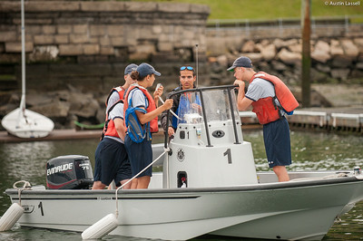 Midshipman Stephen Glass 2nd Classman piloting Whaler 1 with 4th Company Candidates aboard for small boats class on July 16th, 2014. Seen here, Midshipman Glass helps candidates practice operating the radio. When entering and leaving the basin, it is important to communicate times of departure and arrival.