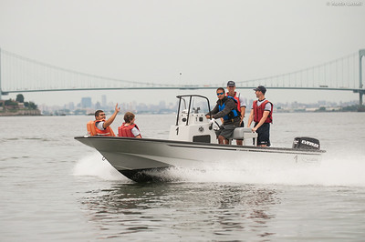 Midshipman Stephen Glass 2nd Classman at the helm of a Whaler with 4th Company candidates aboard returning to campus following obstacle course training at SUNY Maritime College on July 16th, 2014.