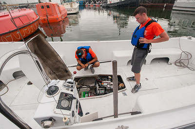 Midshipman Nick Gioino 3rd Classman, on left,  and Midshipman William  3rd Classman, on right, check levels of fluids on a Launcher engine in preparation for for small boats class on the morning of July 16th, 2014.