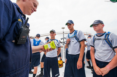 Midshipman Alex Miller 3rd Classman teaches 2nd Company candidates about the use the EPIRB (electronic position indicator radio beacon) during an underway class on the Training Vessel Liberator on July 14th, 2014. The EPIRB is used for alerting port state authorities the location of the abandoned ship during an emergency.