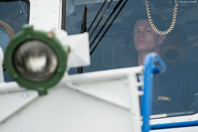 Midshipman Asaro 1st Classman looks out the front window of the bridge while practicing being in charge of the con with Midshipman Samuels 3rd Classman at the helm during an underway class on the Training Vessel Liberator on July 14th, 2014. While both midshipmen are not first timers, but actually in charge of helping run indoctrination events at the Waterfront, there is always much to be learned and practice makes perfect.