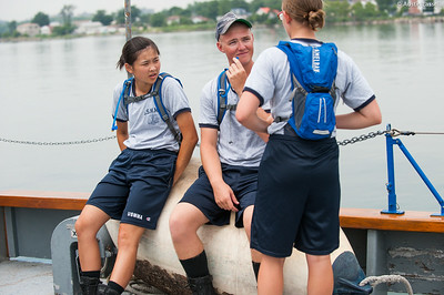 USMMA 2nd Company candidates sit on a large dock bumper and speak to each-other awaiting their next class to be taught on the Training Vessel Liberator during an underway class on July 14th, 2014.
