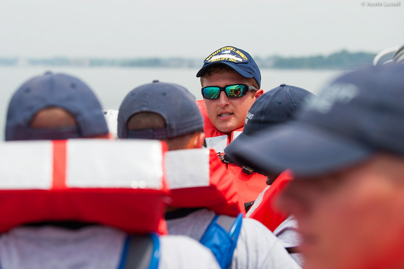 Midshipman Sam Hagen 3rd Classman speaks to USMMA 2nd Company candidates on the importance of certain types of lifejackets during an underway class on the Training Vessel Liberator on July 14th, 2014. The life jackets shown are shaped such that the head of the person wearing the jacket will be held above the water, should they become unconscious.