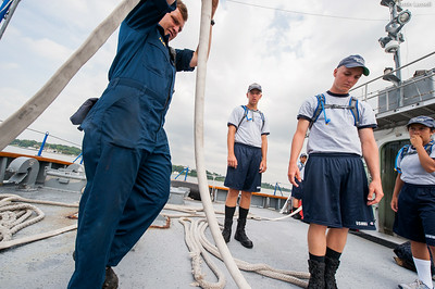 Midshipman Ed Pajus helps clean up following a fire drill at the stern of the ship with a live hose during fire training on the Training Vessel Liberator during an underway class on July 14th, 2014.