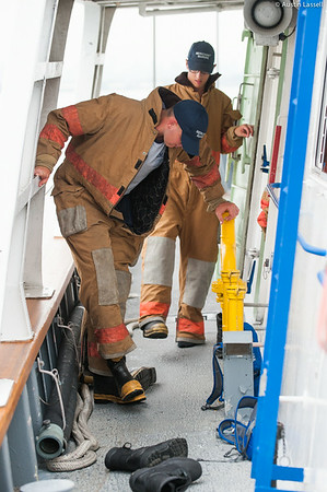 A USMMA 2nd Company candidate removes a fire suit following fire training during an underway class on the Training Vessel Liberator on July 14th, 2014. Fires on a ship are no small matter as the only place to escape to is the water.