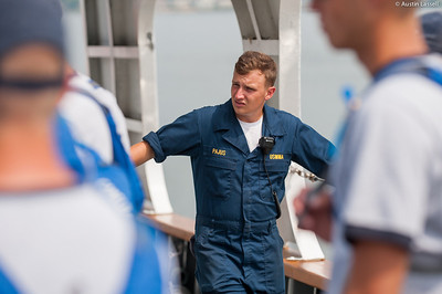 Midshipman Ed Pajus 1st Classman looks on as Captain Jonathan Kabak speaks with USMMA 2nd Company candidates following a simulated man overboard drill during an underway class on the Training Vessel Liberator on July 14th, 2014.