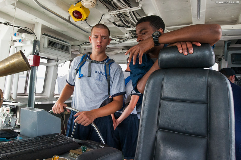 Midshipman Samuels 3rd Classman speaks with a USMMA 2nd Company candidate who is at the helm during an underway class on the Training Vessel Liberator on July 14th, 2014.