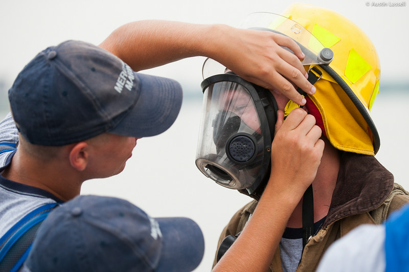 A USMMA 2nd Company candidate helps a fellow candidate remove a fire suit during fire training on the Training Vessel Liberator during an underway class on July 14th, 2014. Fires on a ship are no small matter as the only place to escape to is the water.
