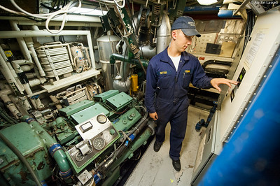 Midshipman Nick Sitter 1st Classman checking the status of one of Liberators two twelve cylinder Detroit Diesel, diesel engines during an underway class on the on July 14th, 2014. Midshipman Sitter is practicing being in charge of the engine room.