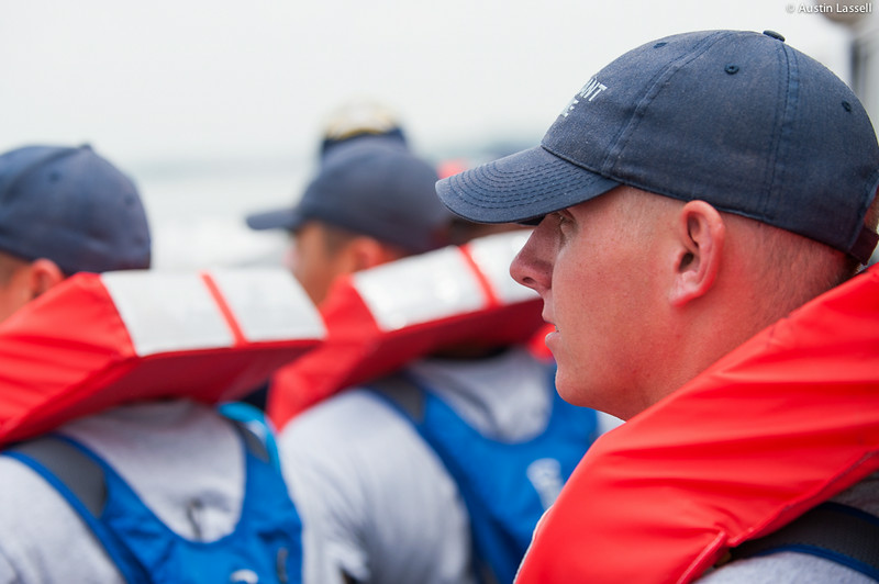 A USMMA 2nd Company candidate pauses momentarily while listening to Midshipman Sam Hagen 3rd Classman speak on the importance of different lifejackets during an underway class on the Training Vessel Liberator on July 14th, 2014. The life jackets shown are shaped such that the head of the person wearing the jacket will be held above the water, should they become unconscious.