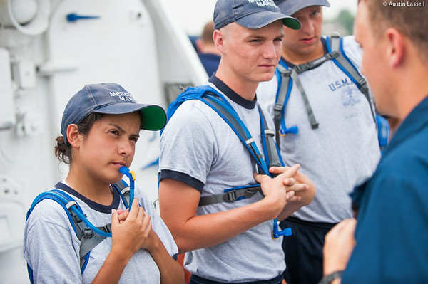 A USMMA 2nd Company candidate listens intently to Midshipman Ed Pajus 1st Classman speak about fire training during an underway class on the Training Vessel Liberator on July 14th, 2014.