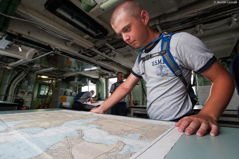 A USMMA 2nd Company candidate puruses a navigation chart in the classroom of the training vessel Liberator during an underway class on July 14th, 2014. Given that the larger the vessel the larger the consequences are for an error, maneuvers must be well thought out and planned.