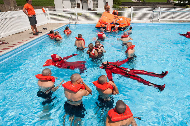 "3rd Company 2nd Platoon candidates practice swimming while wearing ""gumby suits"", and type 1 PFD's during water survival training on July 16th, 2014. In the background a survival life raft can be seen. This raft is meant to seat 6 and is designed to aid in surviving an abandoned ship."