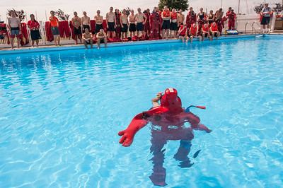 """Midshipman Tyler Redinger 1st Classman  demonstrates the difficult task of putting on the cumbersome survival  """"gumby suit"""" to 3rd Company 2nd Platoon cadidates while in the water during water survival training on July 16th, 2014. The main disadvatage of putting the suit on while in the water is that the suit becomes full of water and incredibly difficult to exit the water while wearing."""