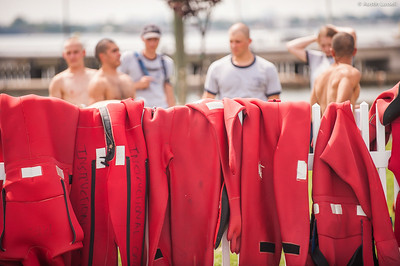 """The fence along the pool in front of Wiley Hall covered in drying survival """"gumby"""" suits following water survival training on July 16th, 2014."""