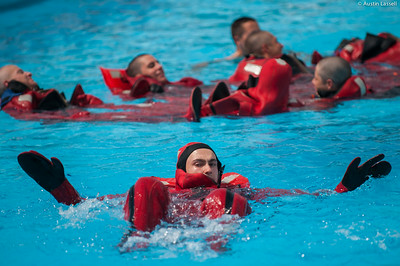 "3rd Company 2nd Platoon candidates practice swimming while wearing ""gumby suits"", and type 1 PFD's during water survival training on July 16th, 2014."