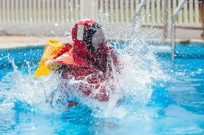 "A 3rd Company 2nd Platoon candidate practicing the proper form of jumping ship while wearing ""gumby suit"", during water survival training on July 16th, 2014."