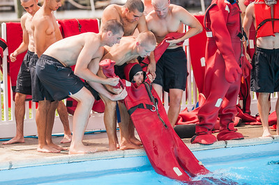 """Midshipman Tyler Redinger 1st Classman  is assisted by 3rd Company 2nd Platoon candidates on exiting the pool after putting on the cumbersome survival  """"gumby suit"""" while in the water during water survival training on July 16th, 2014. With the suit full of water, it is incredibly heavy and difficult to move."""