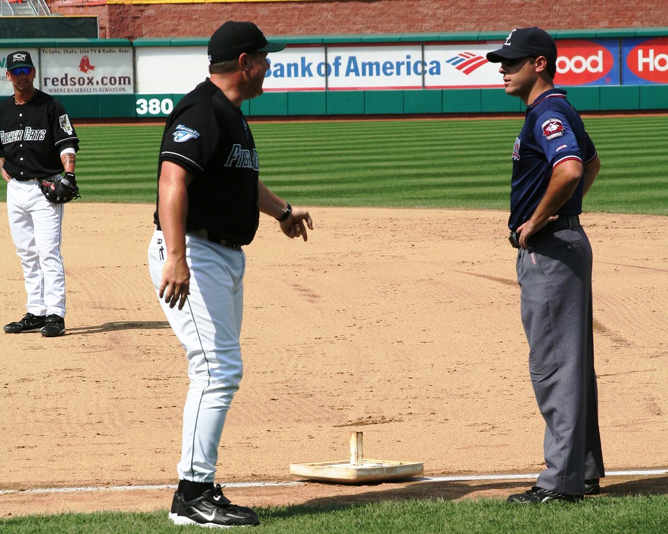 New Hampshire manager Mike Basso lifts the bag from the ground and drops it at the feet of first base umpire Brian Reilly.