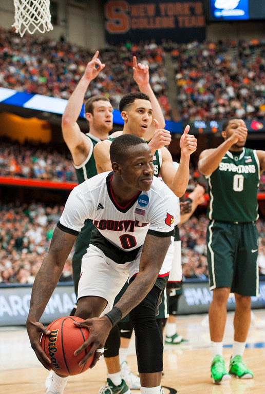 Louisville's Terry Rozier, No. 0, looks to the referee disappointed but understandingly following a jump ball called when his shot was blocked without a foul during a lay up late in the 2015 NCAA Tournament Elite 8 game for the University of Louisville Cardinals VS Michigan State at the Carrier Dome in Syracuse, New York on 03-29-15. The Cards and the Spartans fought well, but the eventually the Spartans were too much for the Cards to overcome. The Spartans defeated the Cardinals in overtime 76-70.