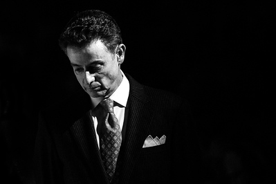 Louisville head coach Rick Pitino of the men's basketball team slowly paces the sidelines while Louisville's game starters are introduced under spotlights before a regular season game for the University of Louisville VS Jacksonville State on 11-17-14 in Louisville, Kentucky at the KFC Yum Center.