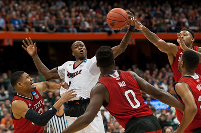 Louisville's Terry Rozier, No. 0, fights the Wolfpack for the ball during the 2015 NCAA Tournament Sweet 16 game for the University of Louisville Cardinals VS the NC State Wolfpack at the Carrier Dome in Syracuse, New York on 03-27-15. The Cards and the Wolfpack were neck in neck for much of the game, but the Cards eventually prevailed in a 75-65 win, much thanks to Rozier who got 14 of the Cardinals' 34 rebounds. The Wolfpack proved throughout the season that they should not be taken lightly, defeating not only the Cards in a tough loss, but also highly ranked Duke, and then defeated the No. 1 seed Villanova in the first round of the tournament.