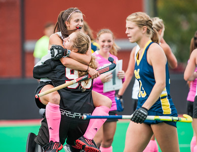 Lotta Kahlert (no. 18)  the women's field hockey team leaps into the arms of goalie Elina Pereira (no .99) in celebration following a goal she scored in double overtime during a regular season game for the University of Louisville VS Michigan on 10-5-14 at Trager Stadium in Louisville, Kentucky.