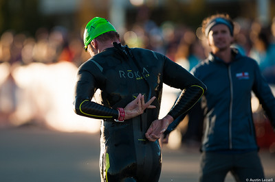 An Ironman Louisville 2016 contestant reaches to remove his wetsuit moments after exiting the water at the completion of the swimming portion of the race in preparation for the next phase of the triathalon, cyclying. The Ironman Louisville 2016 took place on 10-9-16 and is the 10th anniversary of the race occuring yearly in Louisville, Kentucky.