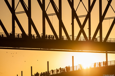 Onlookers atop the Big Four walking bridge look at swimmers competing in the Ironman Louisville 2016, swimming in the Ohio River. The Ironman Louisville 2016 took place on 10-9-16 and is the 10th anniversary of the race occuring yearly in Louisville, Kentucky.