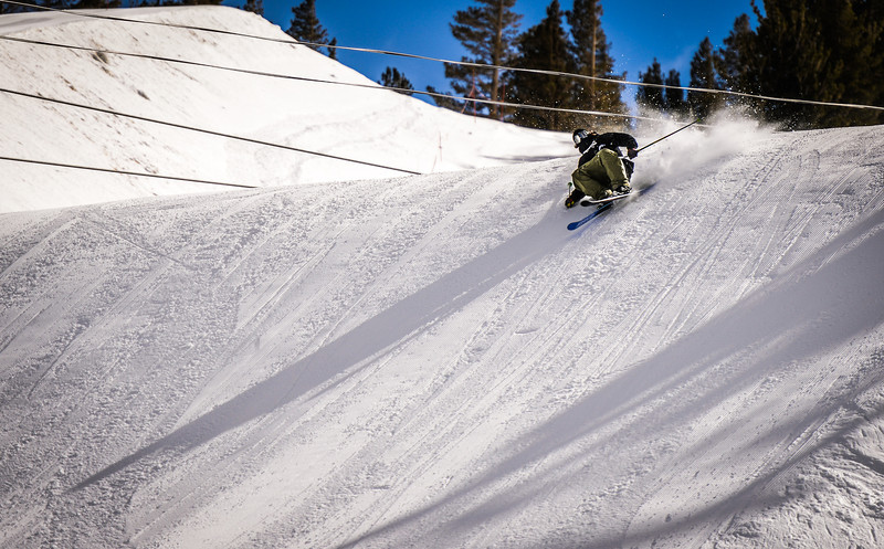 Skier getting close to the snow on his landing Main Snowpark Mammoth Mountain