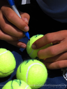 Frank Dancevic (CAN) signing tennis balls.