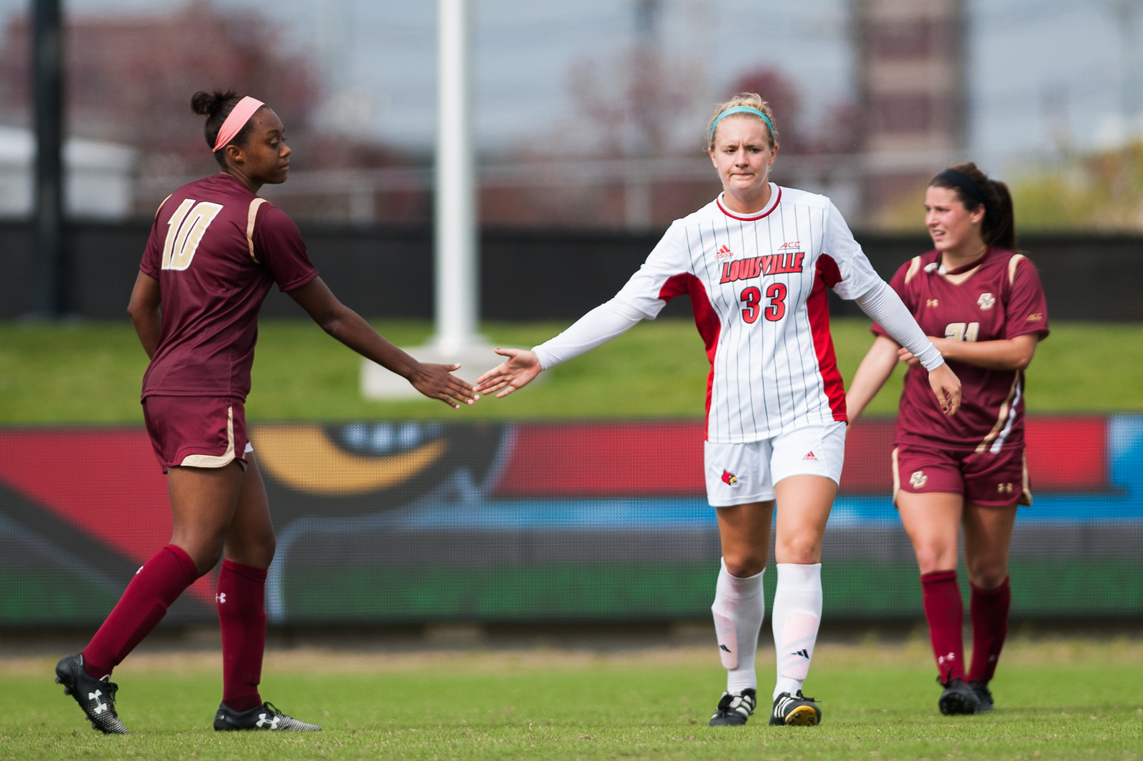 Lexie Niedoba (no. 33) of the women's soccer team frustratingly high-fives an opponent following a 0-1 loss during a regular season game for the University of Louisville VS Boston College on 10-12-14 in Louisville, Kentucky at Lynn Stadium.