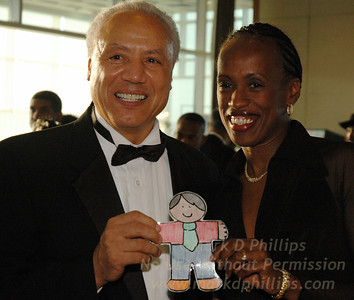 "Lenny Wilkins, head coach of the NY Knicks, and Olympian Jackie Joyner Kersee hold a Flat Stanley for a guest at the Arthur Ashe Institute's 10th Anniversary Sportsball held in New York on April 29. Wilkins was honored with the ""Legacy in Motion"" Award for his work with charity. Photo by Mark D. Phillips"