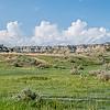 white clouds over green grasslands and badlands