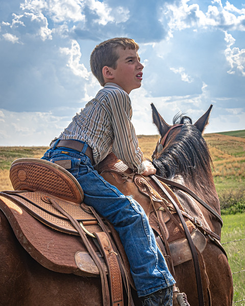 young boy in saddle looks up to right