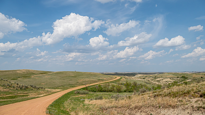 road curves to left under summer skies