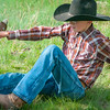 roundup black hat cowboy holds calf rear legs