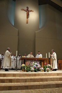 Bishop Luis Zarama, center stands before the altar during the Liturgy of the Eucharist along with (l-r) Deacon Mike Byrne, Father Bryan Small, master of ceremonies, and Deacon Gary Womack. The 10 foot cross made of cherry wood above the altar is the work of Marietta artist and Transfiguration Church parishioner Jorge Posada.