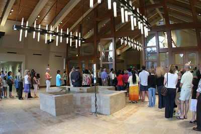 The overflow crowd, which occupied the lower level of the new structure and the old worship space, passes through the narthex on its way into the church to receive holy Communion.