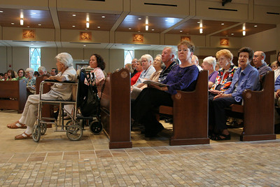 Parishioners gather in their new worship space during the Mass of dedication at St. John Neumann Church, Lilburn. The small pattern of the ceramic tile floor going down the center aisle contrasts the larger, smooth tiles on both sides of it, so the visually impaired can know their whereabouts. The church includes a number of other features to meet the needs of the physically disabled.