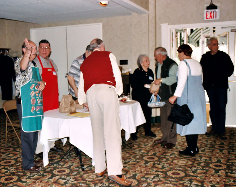 Volunteers pass out bags with blessed fava beans and a blessed bun at the entrance to the St. Joseph Table at Italian American Heritage Foundation banquet hall.