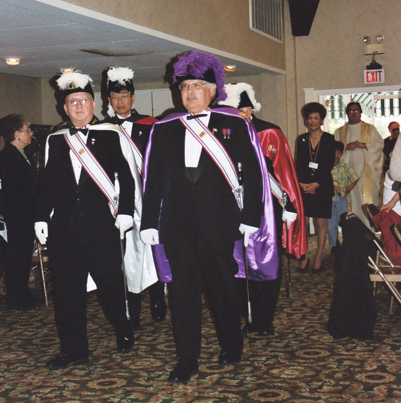 Left to right: Pauline Ciraulo, Members of the Knights of Columbus honor guard, Kathy Dimaria, and Fr. Clair Orso, former pastor of Holy Cross Church. The procession is entering the Italian American Heritage Foundation hall for the Mass at the St. Joseph's Table celebration 2005