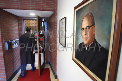 A picture of Fr. Anthony DiMichele pastor St. Mary of the Assumption in 1965 who had the present church built in 1965 hangs on the wall as a parishioner enters the church before mass celebrating St. Mary of the Assumption's 240 years. photo/ www.DonBlakePhotography.com