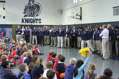 Carroll College defensive tackle Mason Siddick, extending the microphone, leads a cheer before the St. Mary's School students.  The Catholic college football team from Helena, Montana visited the Rome Catholic school while they were in town for the NAIA football championship.