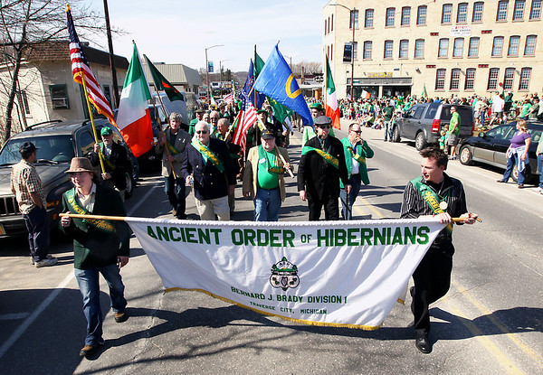 Record-Eagle/Keith King<br /> Leon Kiley, right, and his brother Evan Kiley, both of Traverse City, carry a banner with their fellow members of the Ancient Order of Hibernians Bernard J. Bun Brady Division Saturday, March 17, 2012 during the annual St. Patrick's Day Parade in downtown Traverse City.