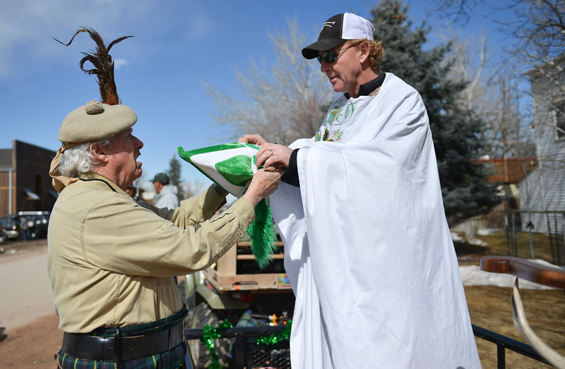 "Justin Sheely | The Sheridan Press<br /> Doug Sheehan, left, offers the St. Patrick costume to Tad Chenoweth during the annual St. Patrick's Day parade in Big Horn Saturday, March 17, 2018. Residents of the unincorporated town of Big Horn take pride in their impromptu ""shortest parade in the world"" every St. Patrick's Day."