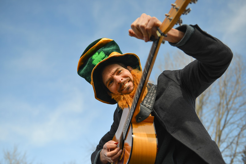 "Justin Sheely | The Sheridan Press<br /> Traditional Irish musician Jon Sousa clamps his guitar during the annual St. Patrick's Day parade in Big Horn Saturday, March 17, 2018. Residents of the unincorporated town of Big Horn take pride in their impromptu ""shortest parade in the world"" every St. Patrick's Day."